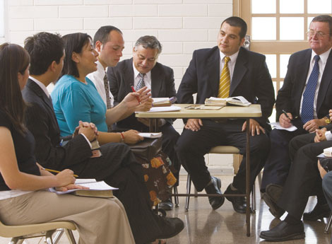 A group of men and women, dressed in Sunday clothes, in a meeting together.