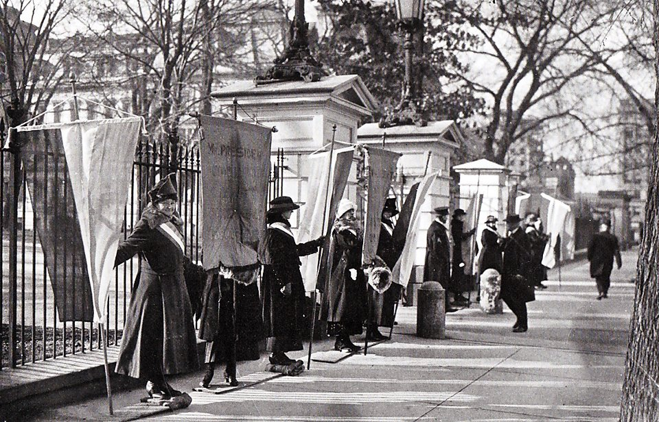 Image: black and white photo of suffragettes lined up in front of the White House