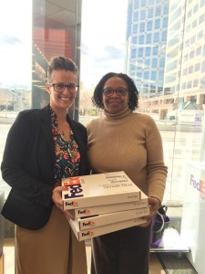 Two women holding four Fed Ex packages.