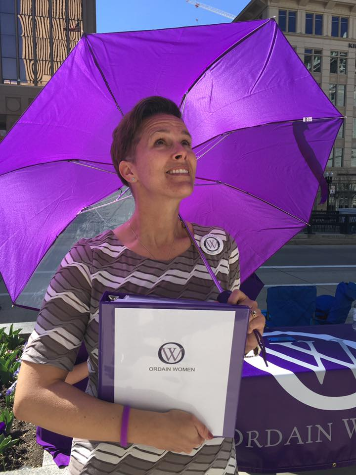 Debra Jenson, standing under an Ordain Women umbrella.