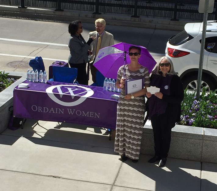Members of Ordain Women's executive board are standing on a sidewalk, around a table that is covered with an Ordain Women table cloth.