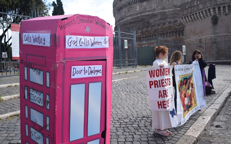 Picture of the Jubilee, a pink confessional booth, and women holding signs
