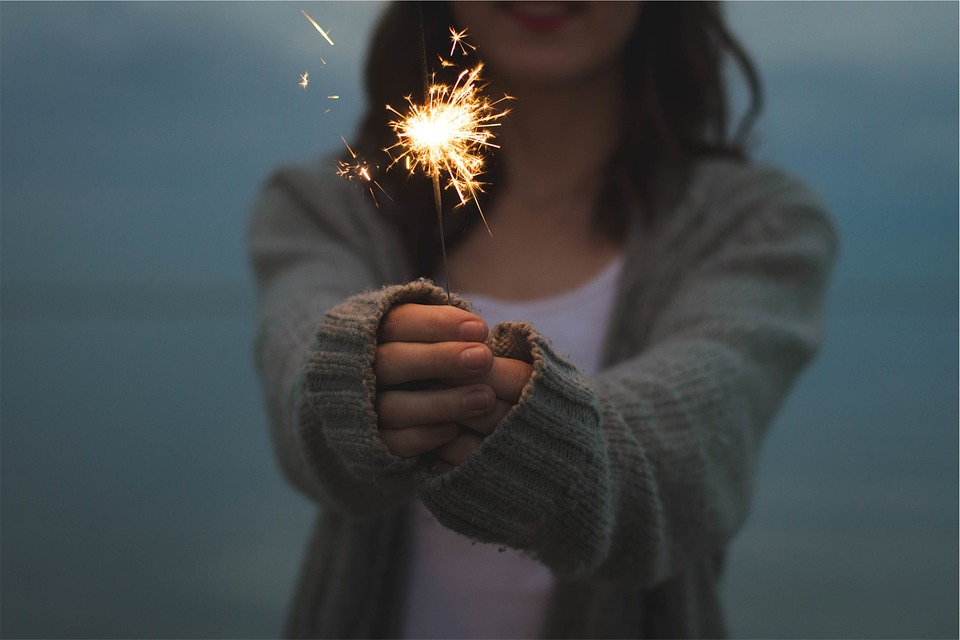 A woman holding out a sparkler.
