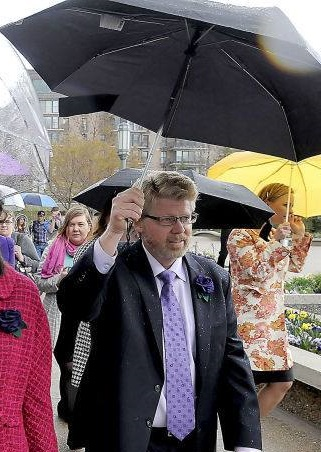 Mark Barnes holding an umbrella at the April 2014 priesthood action.