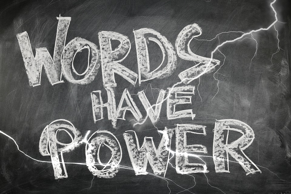 "The phrase ""words have power"" are written in white chalk on a chalkboard, with electricity sparks drawn through the letters."
