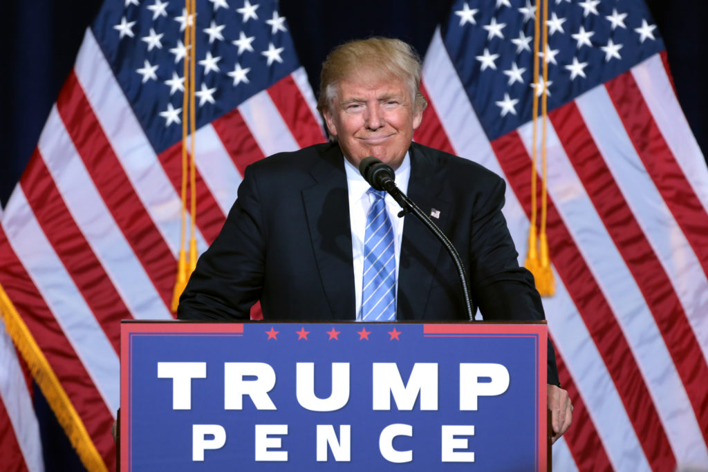 "A picture of Donald J. Trump standing in front of two American flags and behing a podium covered in a sign that says, ""Trump, Pence."""
