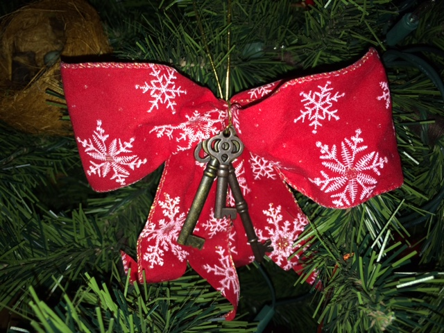 A picture of an ornament hanging from a tree. The ornament is a red Christmas bow, with white snowflakes on the fabric. There are three old-fashion keys hanging from the knot of the bow.