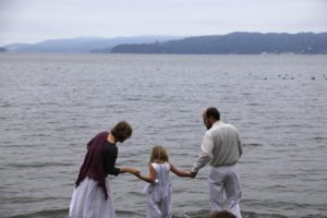 A man and a woman lead a young girl into the ocean. The man and girl are wearing white baptismal clothes.